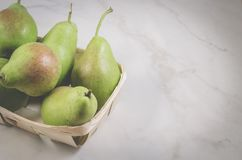 Ripe pears in a wattled box/ripe pears in a wattled box on a white marble background, top view and copy space royalty free stock photos