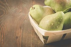 Ripe pears in a wattled box on a wooden background/fresh pears in a wooden box, copy space stock photos