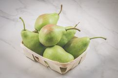Ripe pears in a wattled box/ripe pears in a wooden box on a white marble background, selective focus royalty free stock image