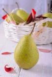 Ripe pears in wicker basket, on wooden background Stock Photo