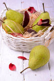 Ripe pears in wicker basket, on wooden background Stock Image
