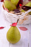 Ripe pears in wicker basket, on wooden background Royalty Free Stock Photos