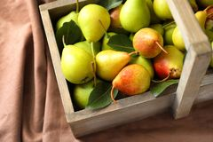 Ripe pears in wooden basket. On fabric Royalty Free Stock Photos