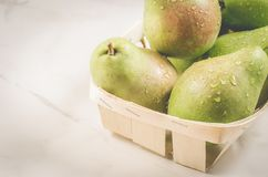 Ripe pears in a wooden box/ripe pears in a wooden box on a white marble background stock photos