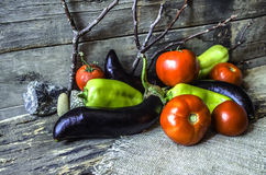 Ripe peppers,tomatoes,and eggplant on of burnt boards Royalty Free Stock Image