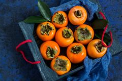 Ripe persimmon in box. With blue gauze napkin on blue textured background. Persimmon is source of vitamin C, iodine, iron, potassium and magnesium. Useful for Stock Photography
