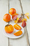 Ripe persimmon with cut Royalty Free Stock Images