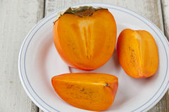 Ripe persimmon with cut Stock Images