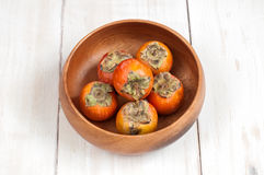 Ripe Persimmon fruit in a wooden bowl Stock Image