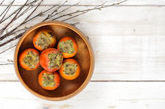 Ripe Persimmon fruit in a wooden bowl with willow twigs Stock Photos