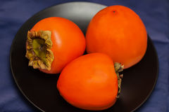 Ripe persimmon fruits in black plate, low key.This ruit is a golden yellow flavorful delicacy from far East Asian origin. Persimmon fruit is a golden yellow Stock Images