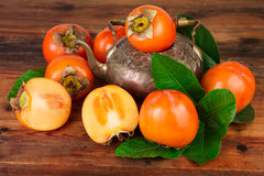 Ripe Persimmon fruits with vintage tea pot. Oriental East Persian still life Stock Photos