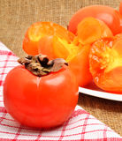 Ripe persimmon fruits on white plate and napking,  sacking backg. Ripe persimmon fruits on the white plate and napking,  sacking background Stock Photos