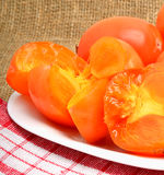 Ripe persimmon fruits on white plate and napking, sacking backgr. Ripe persimmon fruits on the white plate and napking, sacking background Royalty Free Stock Photography