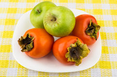 Ripe persimmon and green apples in white plate Royalty Free Stock Photos