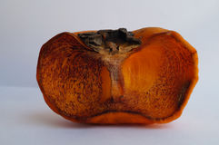 Ripe persimmon. Orange ripe persimmon is withered.you can see black tracery line.It`s japanese persimmon.Nature fruit is rotting.The picture white background and Royalty Free Stock Photos