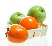 Ripe persimmons and apples Royalty Free Stock Photos