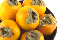 Ripe persimmons in bowl isolated on white Stock Photo