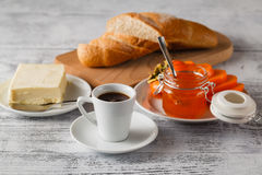 Ripe persimmons with jam in glass saucer and cinnamon on table o Royalty Free Stock Photography