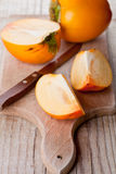 Ripe persimmons and knife Royalty Free Stock Photo
