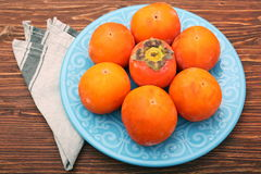 Ripe persimmons on plate Stock Photos