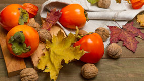 Ripe persimmons. And walnuts on a wooden table Royalty Free Stock Photography