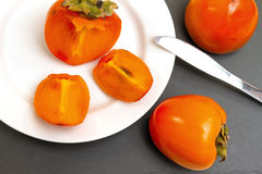 Ripe persimmons. On a white plate on black background Royalty Free Stock Photography
