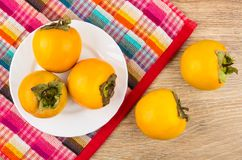 Ripe persimmons in plate on checkered napkin and on table Stock Photos
