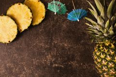 Ripe pineapple and cocktail umbrellas on a dark table with a marble texture with scratches. Cut fruit. Healthy eating. Going on a journey to the south royalty free stock photos