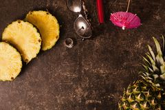 Ripe pineapple and cocktail umbrellas on a dark table with a marble texture with scratches. Royalty Free Stock Photo