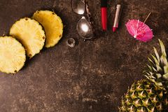 Ripe pineapple and cocktail umbrellas on a dark table with a marble texture with scratches. Stock Photography