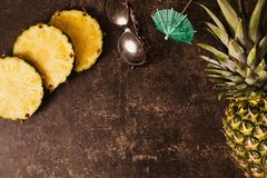 Ripe pineapple and cocktail umbrellas, leopard sunglasses on dark table with a marble texture. With scratches. Cut fruit. Healthy eating. Going on a journey to royalty free stock images