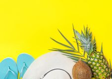 Ripe pineapple coconut on green palm leaf white straw hat blue slippers on bright yellow solid background. Summer vacation fun. Tropical fruits beach party royalty free stock image