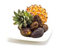 Ripe pineapple and dates on the white Stock Photography