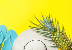 Ripe pineapple on green palm leaf white straw hat blue slippers on bright yellow solid background. Summer vacation fun. Tropical fruits beach party concept royalty free stock photography