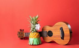 Ripe pineapple in a green skirt. Guitar on a fashionable coral background. Relaxation concept and Hawaiian party. royalty free stock image