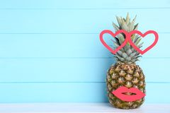 Ripe pineapple with lips and hearts on a blue background stock photo