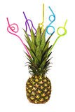 Ripe pineapple with сolorful drinking straws on white. Background Stock Photos