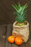 Ripe pineapple in paper bag with oranges on wooden table. Royalty Free Stock Photography