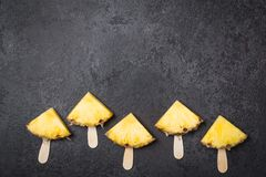 Ripe Pineapple slices on sticks on a black background royalty free stock photo
