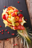 Ripe pineapple stuffed with fresh tropical fruits close-up. Vert Stock Image