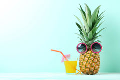 Ripe pineapple. With sunglasses and glass of juice on mint background Stock Images
