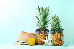 Ripe pineapple with sunglasses. And glass of juice on mint background Royalty Free Stock Photography