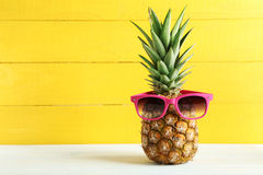 Ripe pineapple. With sunglasses on a white wooden table Royalty Free Stock Photography