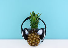 Ripe pineapple wearing sunglasses on blue background. stock photography