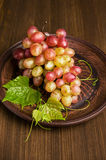 Ripe pink grapes in a clay plate Royalty Free Stock Photo