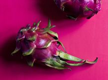 A ripe pitahaya dragon fruit. On a pink background stock image