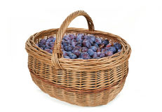 Ripe plums in basket Stock Images