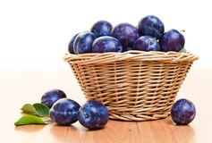 Ripe plums in basket on a wood table Royalty Free Stock Photography