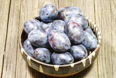 Ripe plums in bowl Stock Photo